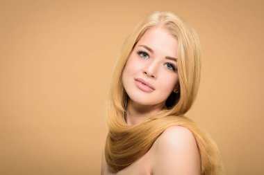 Front view of girl with shiny blonde hair around neck