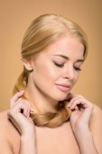 Fotografie beautiful tender naked girl holding blonde hair around neck and looking down isolated on beige