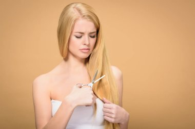 upset young blonde woman cutting long hair with scissors isolated on beige