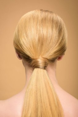 rear view of young blonde woman with long straight smooth hair isolated on beige