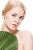 atraktivní nahá žena s zelený list tropické na hrudi při pohledu na fotoaparát izolované na bílém