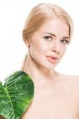 atraktivní nahá dívka s zelený list tropické na rameni při pohledu na fotoaparát izolované na bílém