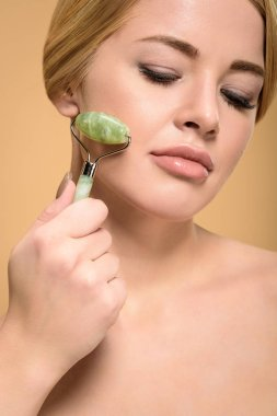 attractive naked girl massaging face with jade roller and looking down isolated on beige