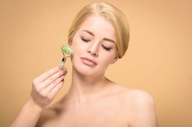 attractive naked woman massaging face with jade roller and looking down isolated on beige