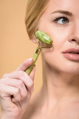 cropped shot of young woman massaging face with jade roller and looking away isolated on beige