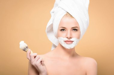 naked woman with towel on head and shaving cream on face holding shaving brush and looking at camera isolated on beige