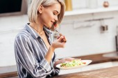 selective focus of attractive woman holding plate and eating lunch