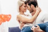 selektiver Fokus der attraktiven Freundin und des gutaussehenden Freundes, der am Valentinstag zu Hause hält und küsst
