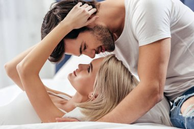 attractive girlfriend and handsome boyfriend kissing in bed