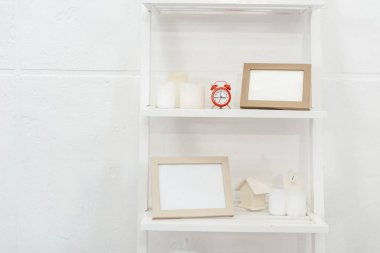 shelves with red clock, wooden frameworks and candles on white background