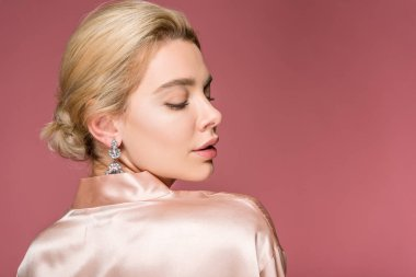 beautiful blonde woman posing in earrings and silk robe, isolated on pink