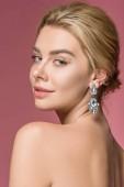 Fotografie attractive naked girl posing in elegant earrings, isolated on pink