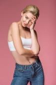 Fotografie schönes lächelndes Mädchen posiert in Jeans und weißen BH, isoliert auf rosa
