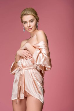 Beautiful blonde woman posing in silk robe, isolated on pink stock vector