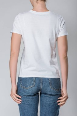 Back view of woman posing in white t-shirt with copy space, isolated on grey stock vector
