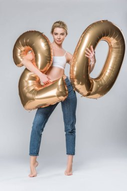 attractive girl in jeans and white bra posing with 20 golden balloons, on grey