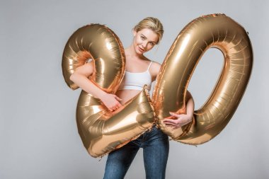 beautiful slim girl in jeans and white bra posing with 20 golden balloons, isolated on grey