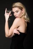 Fotografie sexy žena dívka v černých šatech pózuje s koktejlové sklenice izolované na černém pozadí