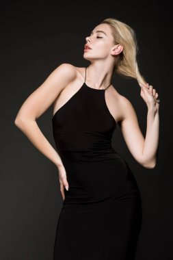 elegant fashionable woman girl in black dress posing isolated on black