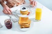 oříznutý pohled na ženu s snídaně s palačinky a pomerančový džus v kuchyni