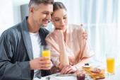 Fotografie handsome man holding orange juice and hugging smiling woman during breakfast in morning