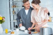 Photo man in robe pouring tea while woman preparing toasts with jam during breakfast
