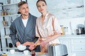 Photo handsome man pouring tea while woman preparing toasts with jam during breakfast