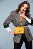 krásná stylová žena v formální oblečení dotýkání obličeje a pózování izolované na šedá