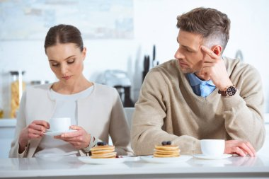 upset woman sitting at table and ignoring man during breakfast in morning
