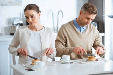 selective focus of adult couple sitting at table and ignoring each other during breakfast in morning