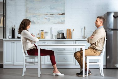 dissatisfied couple looking at each other while sitting with arms crossed at table in kitchen