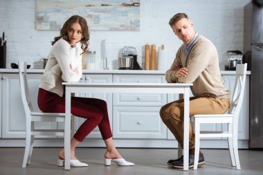 dissatisfied couple sitting with arms crossed at table in kitchen