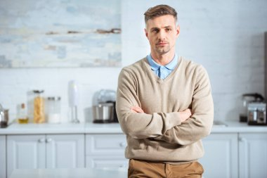 handsome man in casual clothes with arms crossed looking at camera in kitchen