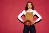 krásná stylová žena v formální oblečení s kožené pouzdro pózuje na červeném pozadí