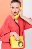 krásná stylová holka mluví o retro telefon a pózování s živých korálů na pozadí