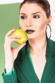 selective focus of beautiful stylish woman holding apple and posing with sea green on background