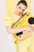 beautiful stylish girl holding retro boombox and posing with limelight on background