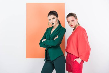 beautiful fashionable young women looking at camera and posing with living coral on background