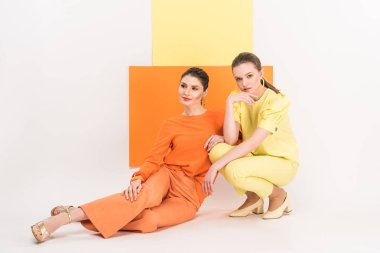 beautiful stylish girls sitting and posing with turmeric and limelight on background