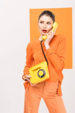 Surprised fashionable young woman talking on retro telephone and posing with turmeric on background stock vector