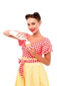 Beautiful pin up girl applying whipped cream on cupcake isolated on white