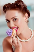 Beautiful pin up girl in pearl necklace tasting homemade cupcake with purple cream