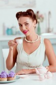 Elegant pin up girl in pearl necklace drinking coffee near plate of cupcakes