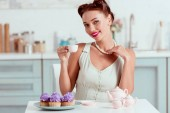 Smiling pin up girl in pearl necklace drinking coffee