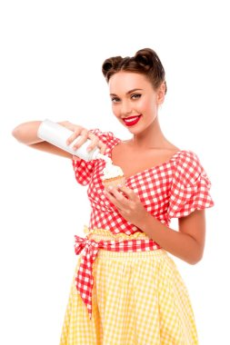 Beautiful pin up girl applying whipped cream on cupcake isolated on white stock vector