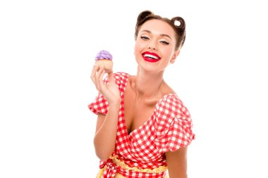 Stylish pin up girl demonstrating cupcake with purple cream isolated on white stock vector