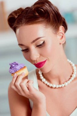 Beautiful pin up woman in pearl necklace holding homemade cupcake