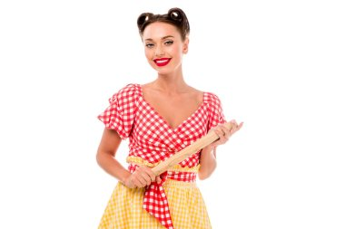 Smiling stylish pin up girl holding rolling pin and looking at camera isolated on white