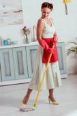Fotografie Pěkný kolík se dívka v červené zástěru a červené gumové rukavice žlutá mop čištění podlahy