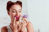 Photo Beautiful pin up girl tasting purple cream of homemade cupcake